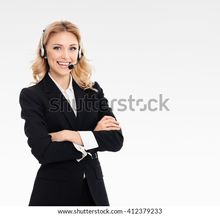 Portrait of happy smiling young support phone operator or businesswomen in headset, on grey background, with blank copyspace area for text or slogan - stock photo