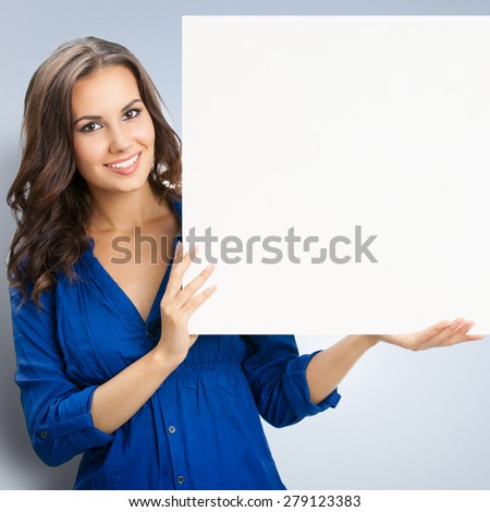 Portrait of happy smiling young woman in blue clothing, showing blank signboard with blank copyspace area for slogan or text - stock photo