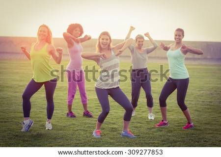 Portrait of happy sporty women dancing during fitness class in parkland - stock photo