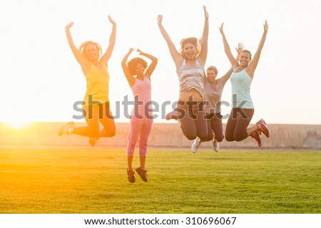 Portrait of happy sporty women jumping during fitness class in parkland - stock photo