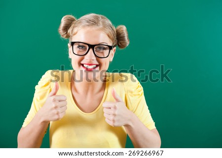 Portrait of happy student girl in front of blackboard - stock photo