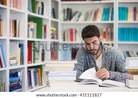 Portrait of happy student while reading book in school library. Study lessons for  exam. Hard worker and persistance concept. - stock photo