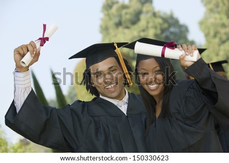 Portrait of happy students holding diplomas on graduation day - stock photo