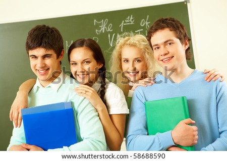 Portrait of happy students standing next to each other and looking at camera with smiles - stock photo