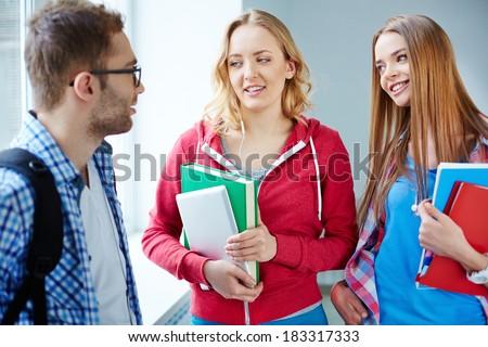 Portrait of happy teen friends talking during break in college - stock photo