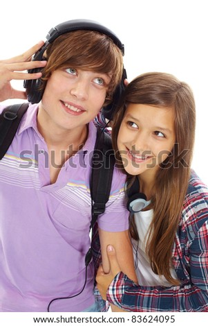 Portrait of happy teenage boy with headphones listening to music while his girlfriend near by trying to hear it - stock photo