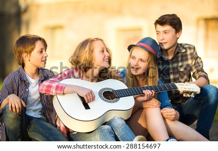 Portrait of happy teens playing the guitar surrounded by  friends - stock photo
