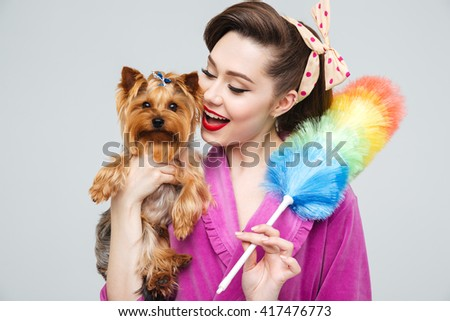 Portrait of happy tender young housewife with cute dog and colorful cleaning broom  - stock photo