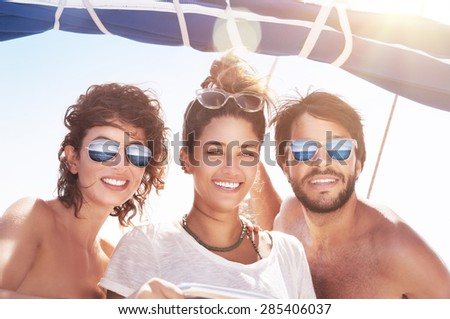 Portrait of happy three people having fun on sailboat, best friends traveling together, enjoying bright sunny summer days in sea cruise - stock photo