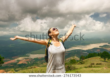 Portrait of happy traveler girl with raised up hands enjoying valley view, mountains landscape, travel to Asia, happiness emotion, summer holiday concept - stock photo