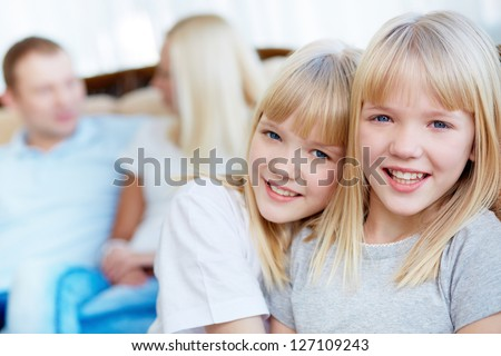 Portrait of happy twin girls looking at camera with their parents behind - stock photo