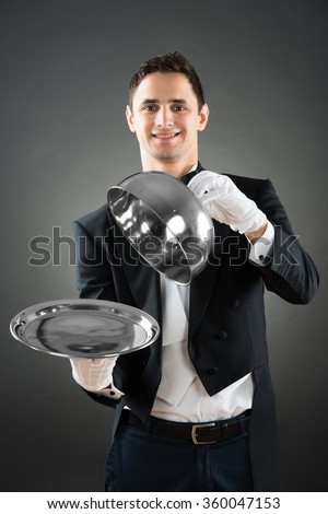 Portrait of happy waiter holding cloche over empty tray while standing against gray background - stock photo