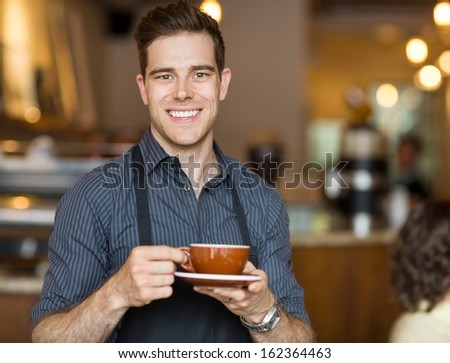 Portrait of happy waiter holding coffee cup while standing in cafeteria - stock photo
