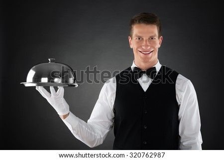 Portrait Of Happy Waiter Holding Stainless Steel Cloche Over Tray - stock photo