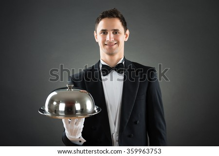 Portrait of happy waiter holding tray with cloche while standing against gray background - stock photo