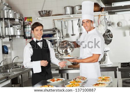 Portrait of happy waiter taking customer's food from chef in commercial kitchen - stock photo