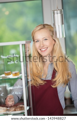 Portrait of happy waitress standing by display cabinet at coffee shop - stock photo