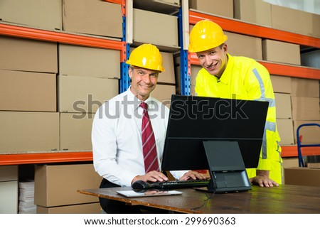 Portrait Of Happy Warehouse Worker And Manager Using Computer In A Warehouse - stock photo