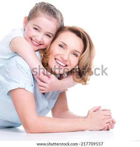 Portrait of happy white mother and young daughter lying on the floor- isolated. Happy family people concept. - stock photo