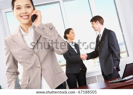 Portrait of happy woman calling on the phone on the background of business people?s handshake - stock photo