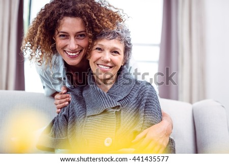 Portrait of happy woman cuddling mother in living room - stock photo
