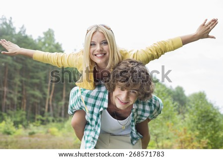 Portrait of happy woman enjoying piggyback ride on man in forest - stock photo