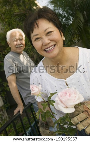 Portrait of happy woman gardening with man standing in background - stock photo