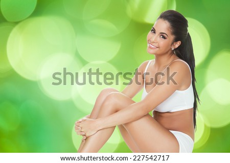 Portrait of happy woman in innerwear sitting against green background - stock photo