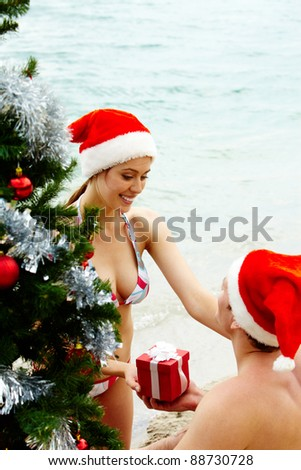 Portrait of happy woman in Santa cap giving giftbox to her husband near xmas firtree on the beach - stock photo