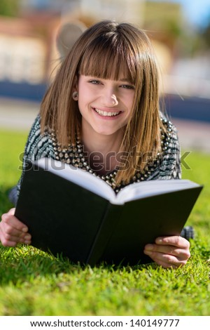 Portrait Of Happy Woman Reading Book In Park, Outdoors - stock photo