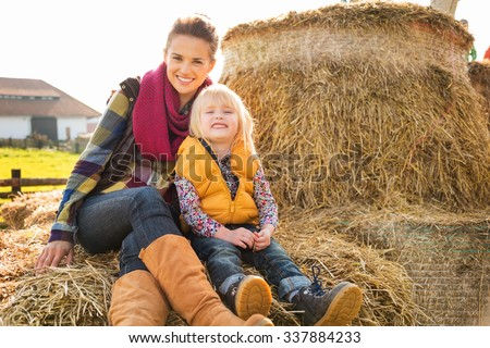 Portrait of happy woman with cute child sitting on the hay on farm on sunny autumn day - stock photo
