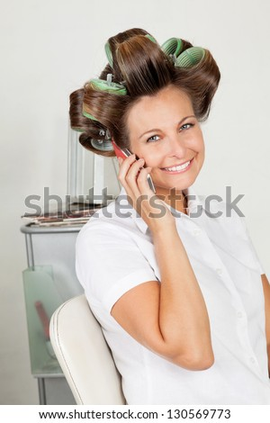 Portrait of happy woman with hair curlers on call at parlor - stock photo