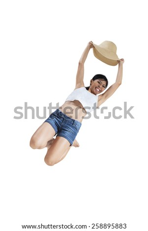 Portrait of happy woman with summer suit and holds a hat, jumping in the studio isolated on white - stock photo