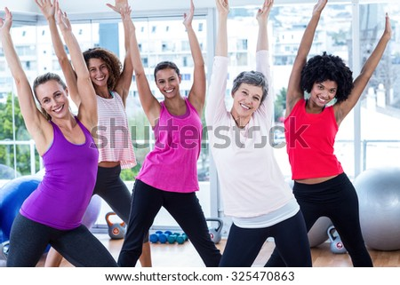 Portrait of happy women exercising with arms raised in fitness studio - stock photo