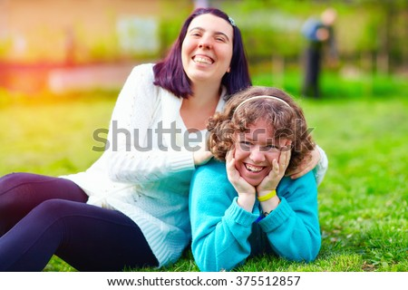 portrait of happy women with disability on spring lawn - stock photo