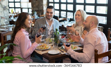 Portrait of happy young adults having dinner in restaurant. Focus on brunette girl - stock photo