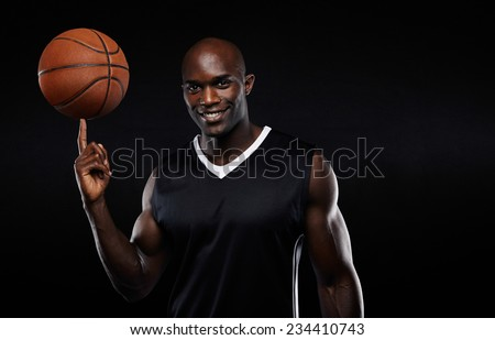 Portrait of happy young african athlete balancing basketball on his finger. Confident basketball player against black background. - stock photo