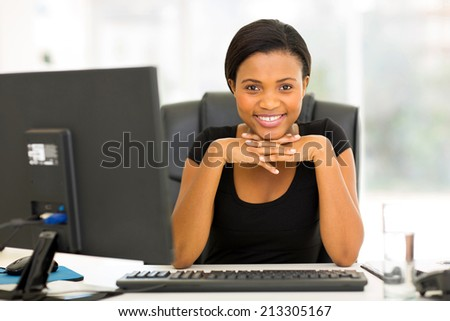 portrait of happy young african business woman sitting in office - stock photo