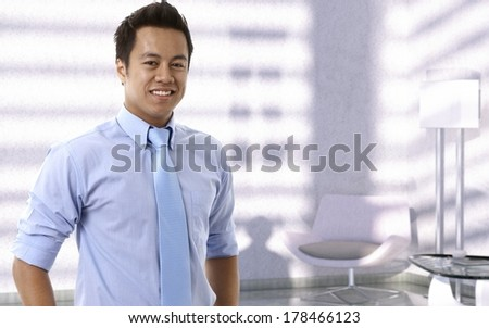 Portrait of happy young asian businessman looking at camera, smiling. - stock photo