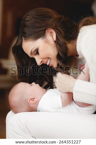 Portrait of happy young attractive mother holding in arms her little adorable baby girl.  Home cozy portrait - stock photo