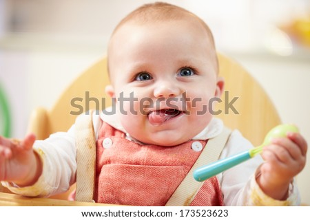 Portrait Of Happy Young Baby Boy In High Chair - stock photo