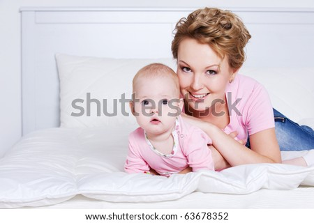 Portrait of happy young beautiful mother lying with her baby on the bed - stock photo