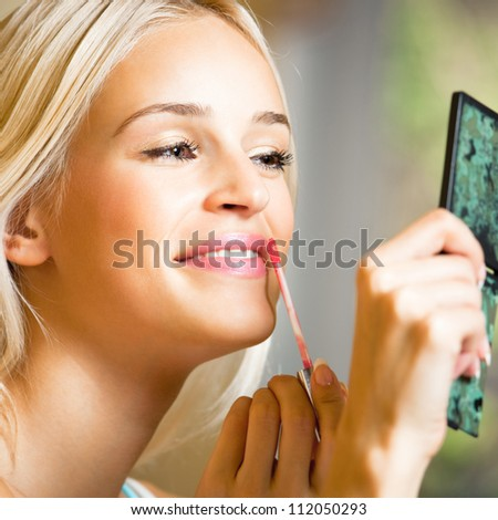 Portrait of happy young beautiful woman applying lipstick at home - stock photo