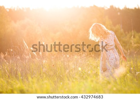 Portrait of happy young blond woman running on a meadow on a sunny summer day. Girl dancing on the grass in the park. Outdoors. Cheerful woman on sunset. Lifestyle and happiness concept - stock photo