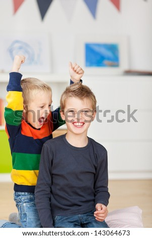 Portrait of happy young boy with mischievous brother raising arms in house - stock photo
