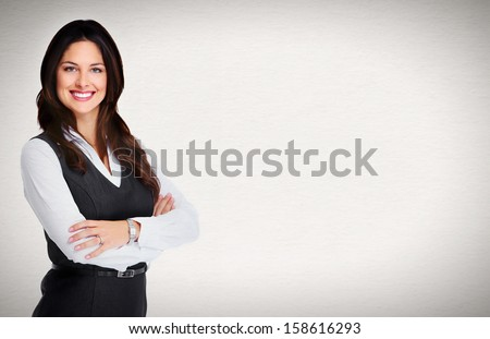 Portrait of happy young business woman standing on grey background - stock photo