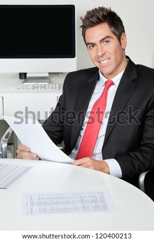 Portrait of happy young businessman holding document while sitting at desk in office - stock photo