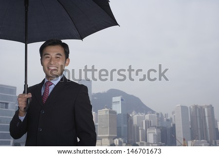 Portrait of happy young businessman holding umbrella with cityscape in background - stock photo