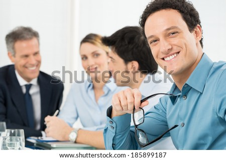 Portrait Of Happy Young Businessman Looking At Camera In Front Of His Colleague - stock photo
