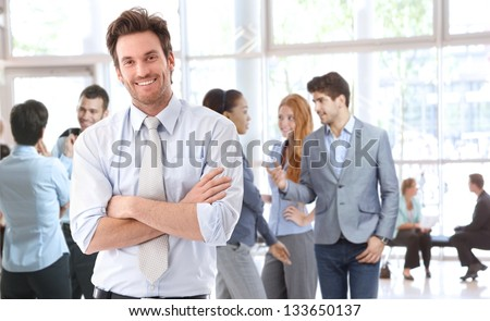 Portrait of happy young businessman standing in office lobby, people talking in background. - stock photo